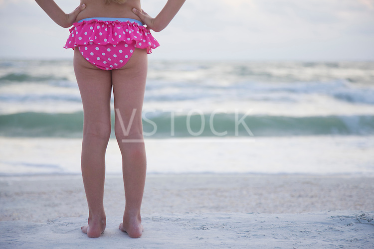 USA, Florida, St. Pete Beach, Rear view of girl (8-9) holding facing ocean, low section