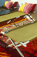 Detail of a row of sun loungers, reminiscent of military camp beds, with colourful striped cushions