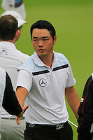 Hu Mu (CHN) finishes his match on the 9th green during Thursday's Round 1 of the 2014 BMW Masters held at Lake Malaren, Shanghai, China 30th October 2014.<br /> Picture: Eoin Clarke www.golffile.ie