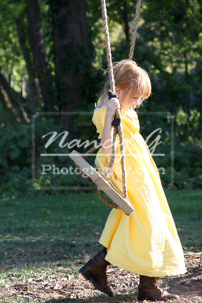 Young girl in a prairie dress getting on a rope swing