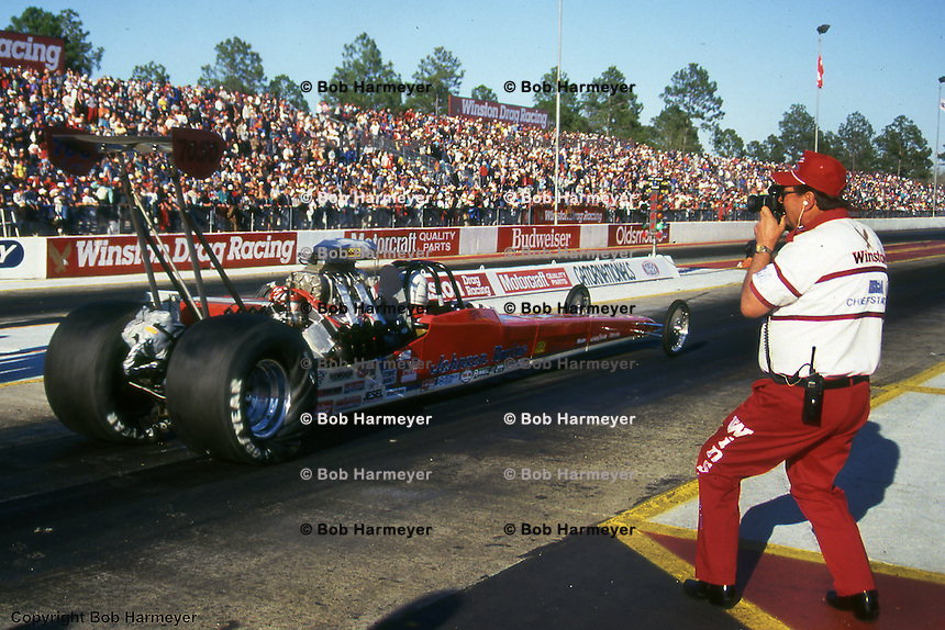 GAINESVILLE, FLORIDA: Buster Couch, NHRA starting line official, shoots a photo at the 1988 race near Gainesville, Florida.