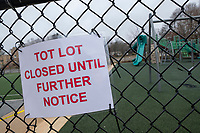 """Caution tape and a sign reading """"Tot Lot Closed Until Further Notice"""" are seen outside the playground at Wellington Elementary during a town-wide facility closure in Belmont, Massachusetts, on Fri., March 20, 2020. Earlier in the week, the Town closed all parks, fields, courts, and playgrounds, as part of the lockdown response to the ongoing coronavirus COVID-19 pandemic."""