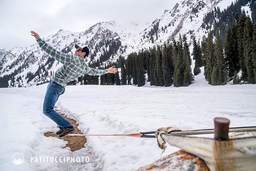 A man slacklining while on a backcountry ski trip in Kyrgyzstan