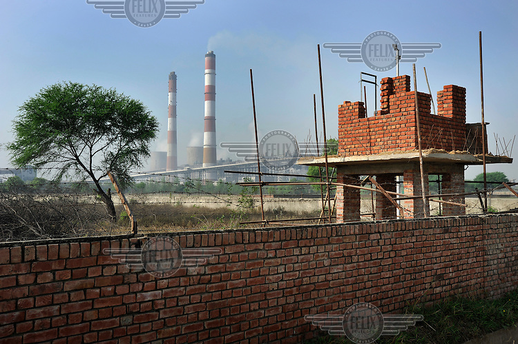 A watch tower being built on the perimeter of the Guru Hargobind Thermal Power Plant. Some of the output of ash from the coal burnt in the plant escapes into the air and has been speculatively linked to health problems in the area.
