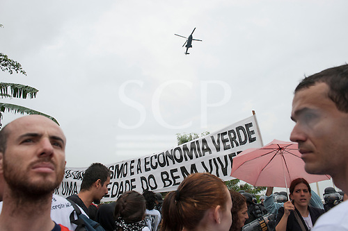 Demonstrators hold a banner while a military helicopter circles overhead at a demonstration in front of the Riocentro United Nations conference. The demonstrators are kept out of earshot and invisible to the UN conference. The United Nations Conference on Sustainable Development (Rio+20), Rio de Janeiro, Brazil, 20th June 2012. Photo © Sue Cunningham.