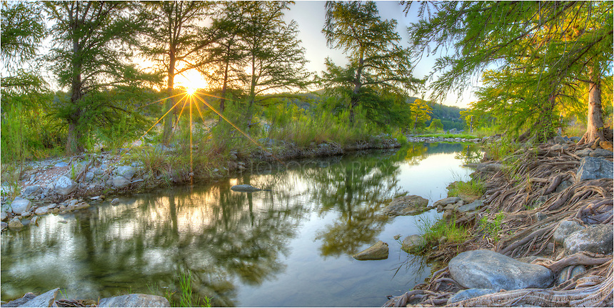 On a warm September morning in the Texas Hill Country, this photograph attempts to capture the peace found along the banks of the Pedernales River in Pedernales Falls State Park. The sun was just beginning to show itself as it rose over the distant cliffs and began to stream into the cypress along the banks. On the right, you can see the gnarled roots of the cypress trees as they twist and turn down to the water's edge.