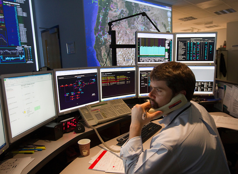 PacifiCorp employee Jabez Masi Pac East Grid Operator, makes a call at a Transmissions Grid Operation center in east Portland, Or. May 27, 2014. PacifiCorp is one of the lowest-cost electricity producers in the United States, providing 1.8 million customers with energy. PacifiCorp has more than 10,500 megawatts of generation capacity from coal, hydro, renewable wind power, gas-fired combustion turbines, solar and geothermal. (Photo by Natalie Behring/ Bloomberg News)