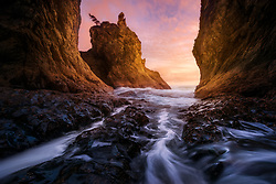 The receding water from an incoming tide flows through this sea cave at sunset, providing a unique perspective on the massive sea stacks on the Olympic Coast.<br />
