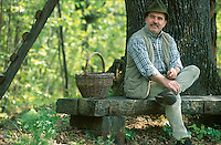 Josko Sirk sitting on a chunky wooden bench in the woodlands around his home