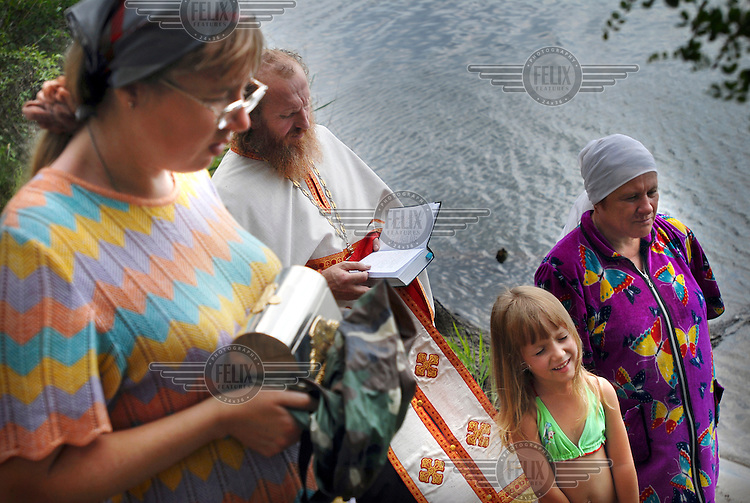 5 year old Paulina is baptised by Russian Orthodox priest Father Alexander in a lake in the countryside near Abakan.