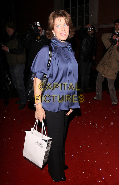 NATASHA KAPLINSKY.Cecile & Hermione English National Ballet's Christmas VIP Party at St Martins Hotel, London, England..December 16th 2009 .full length blue top pregnant maternity collar high neck silk satin black trousers goody bag .CAP/AH.©Adam Houghton/Capital Pictures.