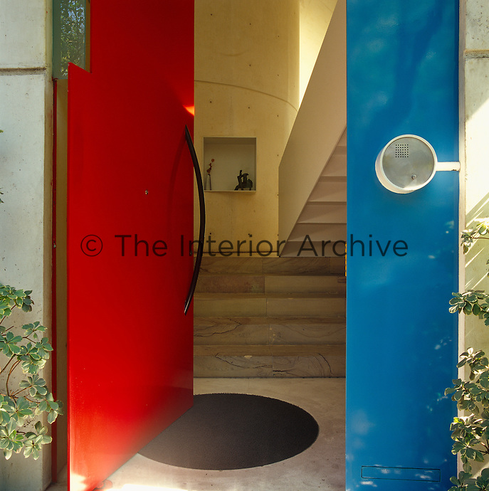 The entrance to this modern house is marked by a bright red and blue front door