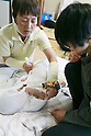 A therapist wraps a baby in cloth in a practice known as Ohinamaki on February 4, 2017, Tokyo, Japan. Parents wrap their babies to give them a feeling of security and help them with their physical development. The Japanese therapeutic method Otonamaki, which translates as ''adult wrapping'' is based on the practice of Ohinamaki to reduce stiffness and posture problems. The therapy  is monitored by a health care professional where participants are wrapped in a large piece of breathable cloth, like a sheet, for about 15 to 20 minutes. (Photo by Rodrigo Reyes Marin/AFLO)