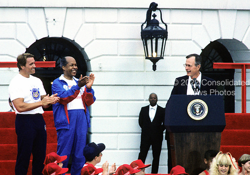 United States President George H.W. Bush, right, makes remarks as he and first lady Barbara Bush kick-off the Great American Workout Month with Arnold Schwarzenegger, left, and US Secretary of Health and Human Services Louis Sullivan, center, on the South Lawn of the White House in Washington, D.C. on May 1, 1990.<br /> Credit: Howard L. Sachs / CNP