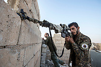 August 2017. Raqqa, Syria.<br /> A member of the MFS tries to locate ISIS positions from the roof of their nocter (base) on the western front lines of Raqqa, Syria.<br /> The MFS (Syriac Military Council) are a group of Assyrian Christians who fight alongside the Syrian Democratic Forces in the fight to topple ISIS.<br /> Photographer: Rick Findler
