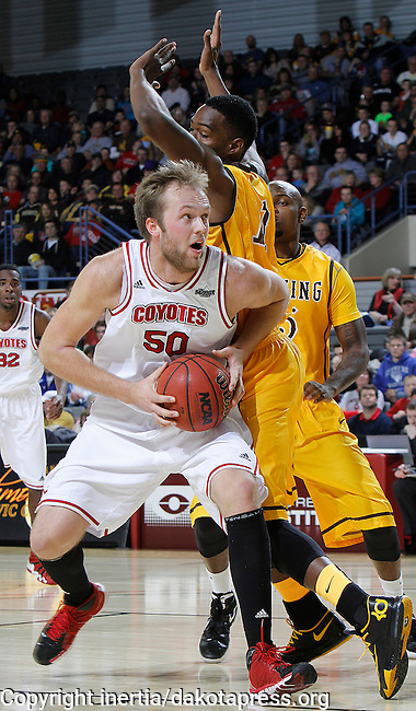 RAPID CITY, S.D. -- DECEMBER 7, 2013 -- Trevor Gruis #50 of the University of South Dakota drives around Derek Cooke Jr. #11 of the University of Wyoming during their game Saturday at the Rushmore Plaza Civic Center Ice arena in Rapid City, S.D.  (Photo by Dick Carlson/Inertia)