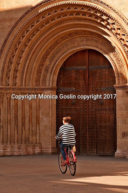 A woman riding a bike, passes the door of Valencia Cathedral, built between the 13th and 15th century