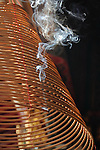 Bao-jhong Yi-min Temple, Kaohsiung -- Sunlit smoke rising from an incense coil under the temple roof.