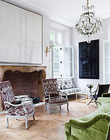 In the family room opens on to the garden terrace and has a light and airy atmosphere. A curving green sofa faces the antique fireplace surround; the 19th-century gilt bronze-and-crystal chandeliers are French.