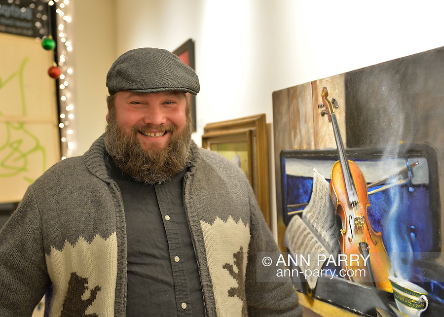 A smiling bearded young man wearing an outdoorsy sweater with bears on it views a musical themed painting of a violin and sheet music, at the Jingle Boom Holiday Bash has entertainment featuring Spoken Word Performances and Live Music, plus windows decorated by artists, and prizes for people wearing the most creative or Ugly Sweaters, at the Main Street Gallery of Huntington Arts Council. Sparkboom, an HAC project, provides events such as this geared to Gen-Y, 18-34 years of age, to address the 'brain drain' of creative young professionals of Long Island. The paintings on the art gallery walls were the Annual Juried Still Life Show.