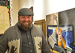 Huntington, New York, USA. February 20, 2014. A smiling bearded young man wearing an outdoorsy sweater with bears on it views a musical themed painting of a violin and sheet music, at the Jingle Boom Holiday Bash.
