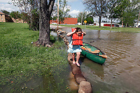 Loveta Miller, 7, of Benton, climbs out of a canoe in the yard of Bill Sandquist in the Red Star District of Cape Girardeau, MO, on Thursday, April 28, 2011.