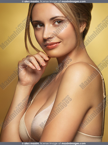 Beautiful smiling glamorous young woman in underwear with romantic daydreaming expression isolated on shint golden background in gold colors