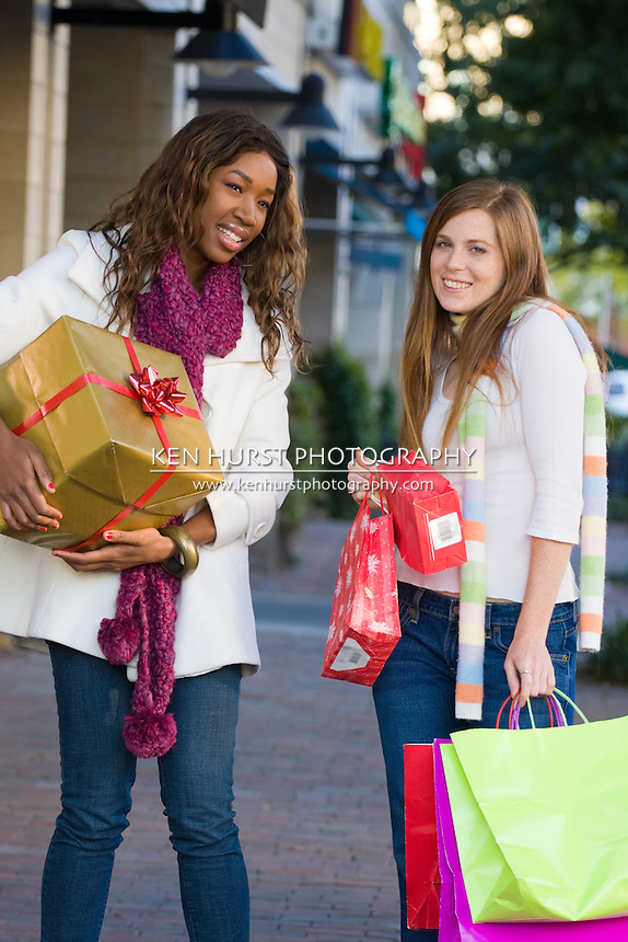 Two attractive young happy women walking in an urban city environment and carrying Christmas gifts.