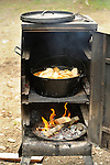 Camp stove with fire and chicken stew cooking.
