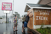 August 27, 2011. Grandy, NC.. Jimmy, right, only name given, worked in driving rain to finish boarding up the Tobacco Barn as co-owner Angela White, left, stood by.. As Hurricane Irene started to make landfall along the North Carolina coast, residents who decided to stick out the storm braced for its arrival.