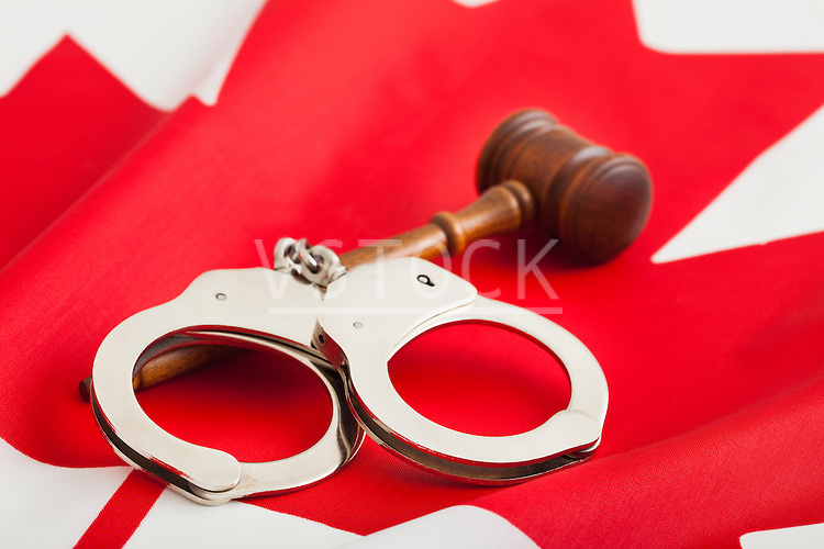 Handcuffs and gavel on Canadian flag