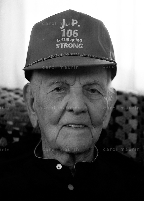 Happy 106 year old man with his age on his hat