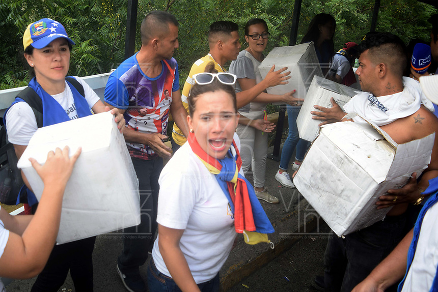 CÚCUTA - COLOMBIA, 23-02-2019: Voluntarios ayudan a descargar los camiones incinerados, durante el intento de ingreso de ayuda humanitaria a Venezuela, en el Puente Francisco de Paula Santander, en la frontera Colombo Venezolana, en la ciudad de Cúcuta. El gobierno de Nicolás Maduro ha cerrado todos los puntos de la frontera con Colombia. / Volunteers help to unload the incinerated trucks, during the attempt of entrance of humanitarian aid to Venezuela, in the Francisco Bridge of Paula Santander, in the Colombo Venezuelan border, in the city of Cúcuta. The government of Nicolás Maduro has closed all the points of the border with Colombia./ Photo: VizzorImage / Manuel Hernández / Cont.