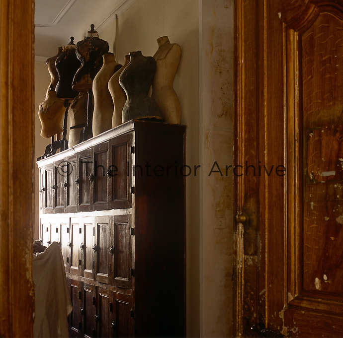 A view through an open door to a collection of wooden mannequins are displayed on the top of a wooden set of lockers.