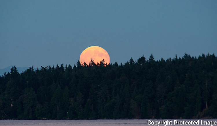 A  super full moon rises over Blake Island near Manchester, Washington on July 26, 2015.   ©2015. Jim Bryant Photo. All Rights Reserve