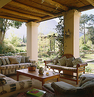 The covered veranda is an extension of the indoor living room and comfortably furnished