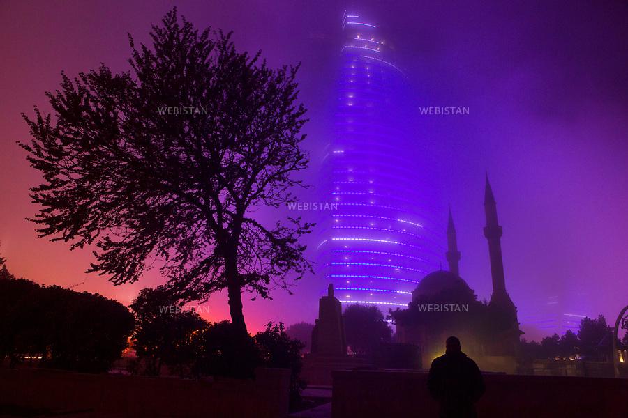 Azerbaijan, Baku, Alley of Martyrs, April 19, 2012<br /> One of the illuminated glass flame towers glows at night behind the Turkish Mosque, also known as the Mosque of the Martyrs. Inspired by Azerbaijan&rsquo;s history of fire worship, the glass high-rises are the tallest skyscrapers in Baku. The construction of the three glass high-rises was completed in 2012 and all three buildings are covered in LED screens that continuously change color at night.<br /> <br /> Azerba&iuml;djan, Bakou, All&eacute;e des Martyrs, <br /> 19 avril 2012 <br /> Une des tours de verre des &quot;Flame Towers&quot; <br /> (&laquo; tous des flammes &raquo;), illumin&eacute;e de nuit, derri&egrave;re la mosqu&eacute;e turque connue sous le nom de &laquo; la Mosqu&eacute;e des Martyrs &raquo;. Inspir&eacute;es par l&rsquo;adoration du feu dans l&rsquo;histoire de l&rsquo;Azerba&iuml;djan, les tours sont les plus hauts gratte-ciel de Bakou. La construction des trois &eacute;difices en verre est achev&eacute;e en 2012 et les b&acirc;timents sont couverts d&rsquo;&eacute;crans LED qui changent continuellement de couleur la nuit.