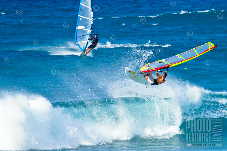 Windsurfer catches air riding surf off Hookipa Beach, Maui.