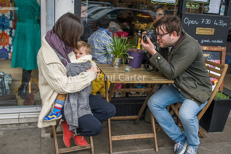 A mother breastfeeds her 15 month old boy from a sling while sitting outside a cafe.  Her partner is taking pictures of them with his camera.<br /> <br /> London, England, UK<br /> 22-03-2015<br /> <br /> © Paul Carter / wdiip.co.uk