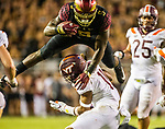 Florida State running back Jacques Patrick (9) leaps over Virginia Tech defensive lineman Houshun Gaines (11) an NCAA college football game between Florida State and Virginia Tech in Tallahassee, Fla., Monday, Sept. 3, 2018. (AP Photo/Mark Wallheiser)