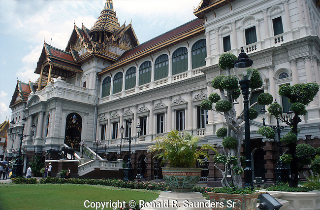 The modern central court is dominated by the curious Chakri Maha Prasat hall. The hall was built by King Rama V and completed in 1882. Its unusual design is due to some controversy during its construction. The original architect was a Briton working in Singapore named John Clunich. Rama V wanted an entirely western look to his new home, but others in the court argued that the king's residence and throne hall should reflect Siamese motifs. Thus the domed roof was replaced by a Thai styled roof. It should be no surprise that the Thai nickname for the building is the 'westerner with a Thai hat'.