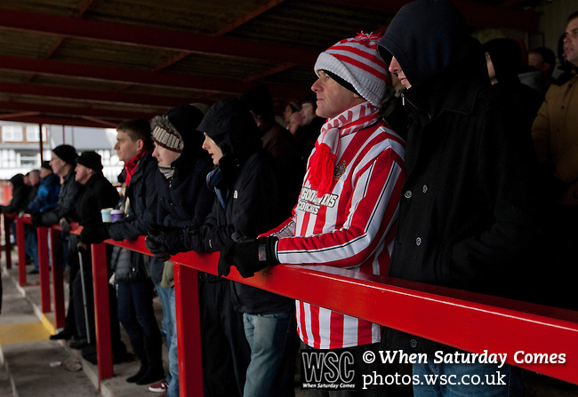 Altrincham 2 Worcester City 0, 23/03/2013. Moss Lane, Blue Square Bet North. A home-team supporter a wearing woollen hat watching the action during the second-half of the the Blue Square Bet North fixture between Altrincham (in red) and Worcester City at Moss Lane, Altrincham. The home team won the match 2-0 watched by 777 spectators on a day when most non-League football in England was cancelled due to adverse weather. Altrincham were historically one of the major English non-League teams but have never been promoted to the Football League. Photo by Colin McPherson.