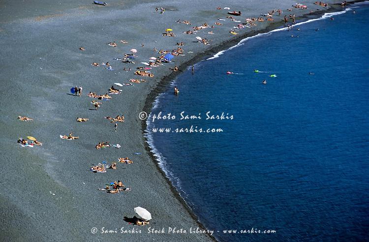 Sunbathers on a black sand beach, Cape Corse, Corsica, France.