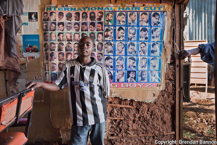 Homeboyz Kinyozi barber Stanley Okukumba, 21 years old, earns up to 800 KSH or $10.00 a day cutting hair at his shop in Kibera, nairobi Kenya's largest slum settlement.