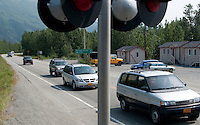 Vehicles returning from Whittier and Portage wait at the crossing for the Chugach Explorer to pass.