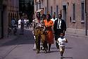 Ghananian immigrants walks along Torre street after have attended to Pentecostal service, Sunday, Nonantola, June 28, 1996..  .Nonantola (Modena), domenica in via della Torre, immigrati ghanesi all'uscita dalla funzione pentecostale.