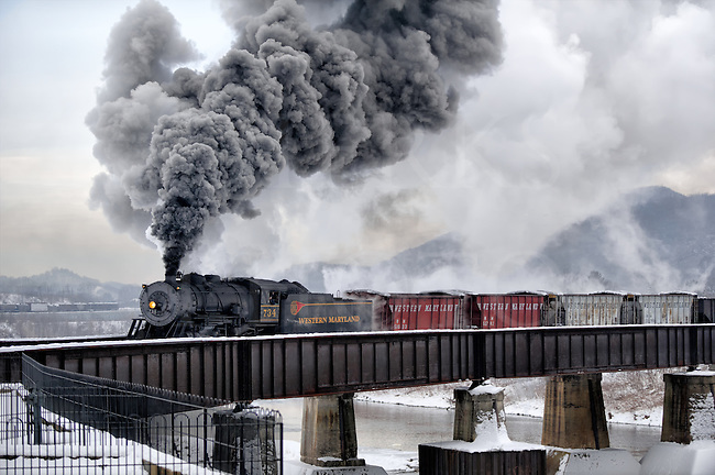Crossing the Potomac River from the Ridgley WV yards and shops, and into the station across the river at Cumberland MD, this reenactment on the old Western Maryland was done on a fifteen degree morning. Good thing, too. We may not have a lot of sunlight under that winter overcast, but look at all the great smoke!<br />