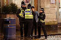 Pictured: A man is spoken to by three police officers. Sunday 31 December 2017 and 01 January 2018<br /> Re: New Year revellers in Wind Street, Swansea, Wales, UK