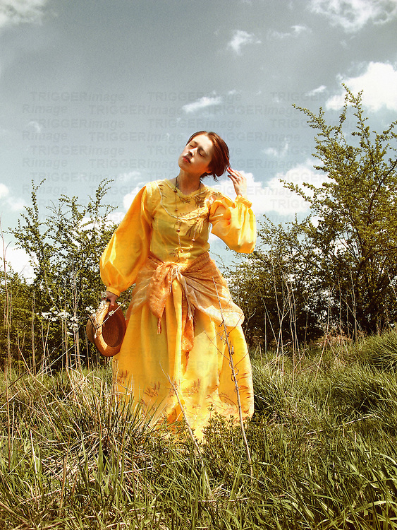 A woman in a long yellow dress, holding a hat and touching hair, walking  in a garden.