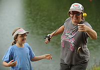 NWA Democrat-Gazette/ANDY SHUPE<br /> Nalah Villneff, 10, of Elkins (left) gets a hand from her mother, Bethany Fitzpatrick Thursday, June 15, 2017, after catching a fish in Carter Pond during the annual Elkins Public Library Fishing Derby in Elkins. Prizes were awarded in several categories for children 16 and under before lunch was served.